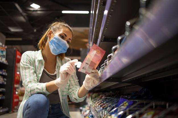 スーパーマーケットで食べ物を買うマスクと手袋を持つ女性