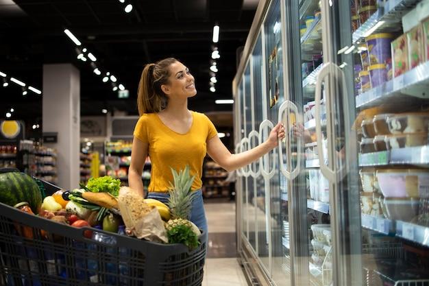 Женщина с тележкой для покупок и берет замороженные продукты из холодильника в продуктовом магазине