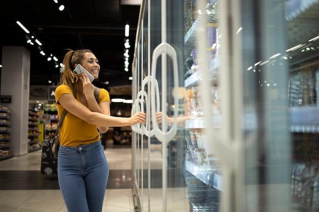 電話で話している間食料品店で食べ物を取るために冷蔵庫を開くショッピングカートを持つ女性