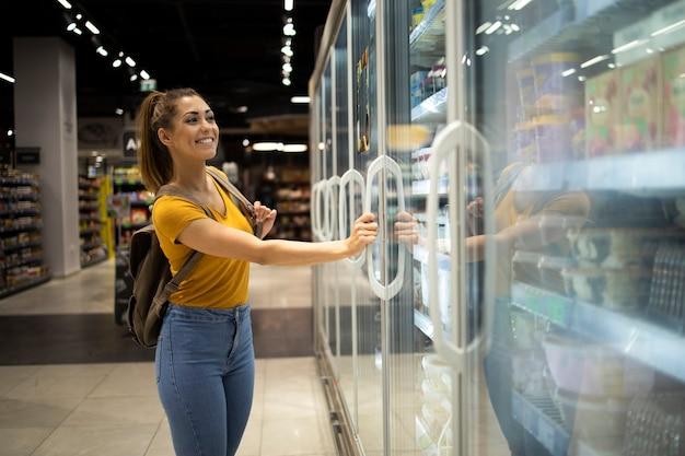식료품 점에서 음식을 가져 가기 위해 냉장고를 여는 쇼핑 카트를 가진 여성 사람