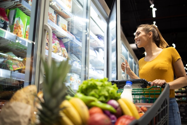 Female person with shopping cart and taking frozen food from the fridge in grocery store.