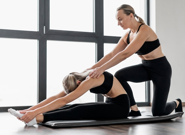 Female personal trainer and her client doing exercises