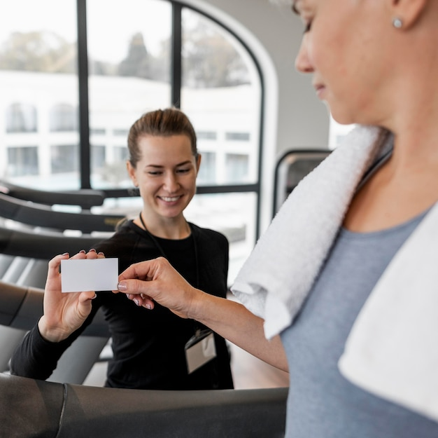 Female personal trainer and her client holding a card