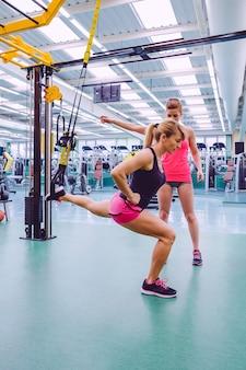 フィットネスセンターでフィットネスストラップを使用したハードサスペンショントレーニングで女性に教える女性パーソナルトレーナー