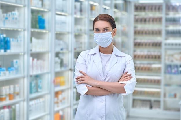Женщина-фармацевт со скрещенными руками стоит в аптеке
