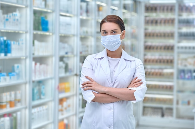 Female pharmaceutist with her arms crossed standing at a drugstore