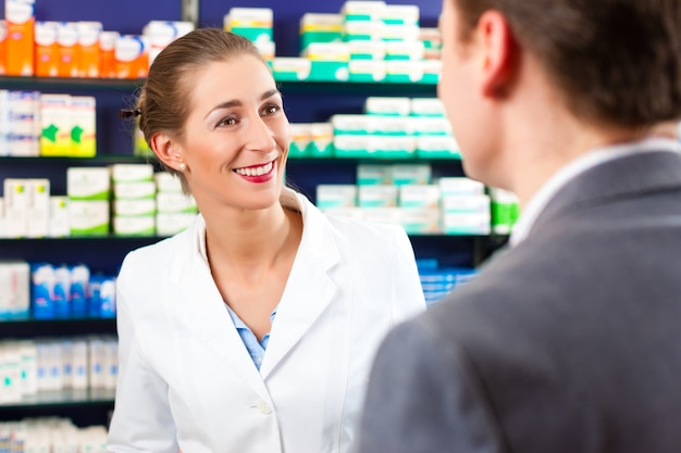 Female pharmacist consulting a customer in pharmacy