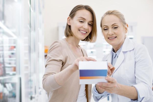 Фармацевт-женщина помогает молодой женщине