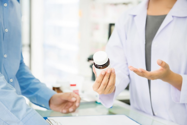 Female pharmacist holding medicine bottle giving advice to customer in pharmacy