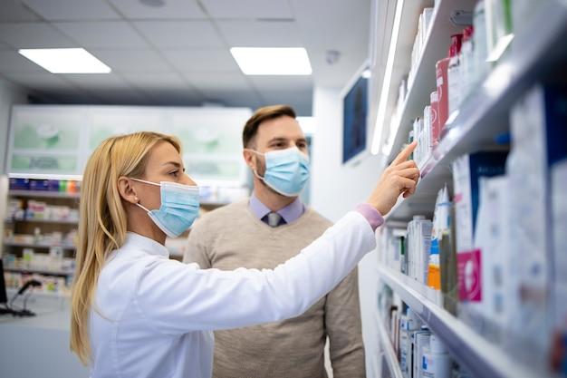 Женский фармацевт, продающий новые продукты покупателю в аптеке.