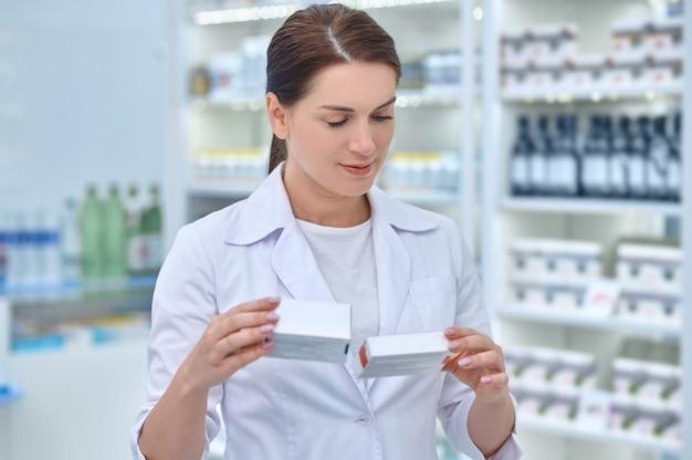 Женщина-фармацевт смотрит на упакованные фармацевтические препараты в руках