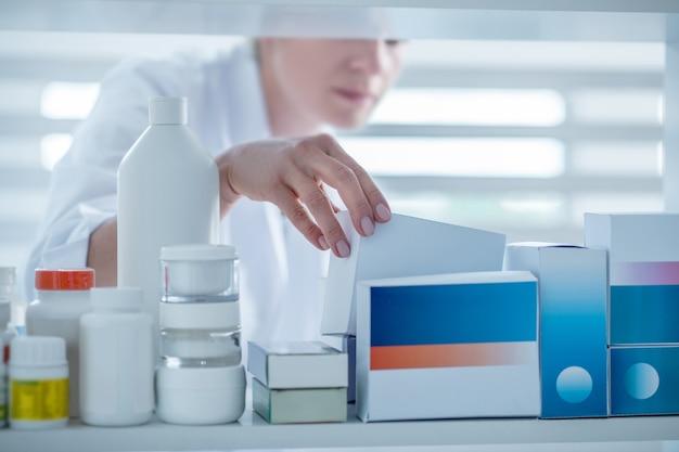 Женщина-фармацевт, принимая лекарство с полки