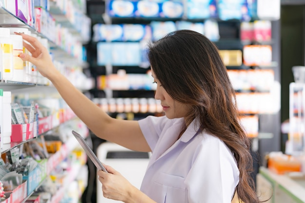 Female pharmacist taking a medicine from the shelf and uses digital tablet in the pharmacy