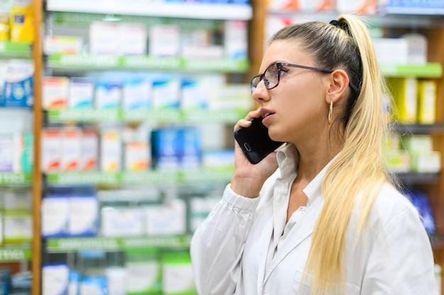 彼の店で顧客と電話で話している女性薬剤師
