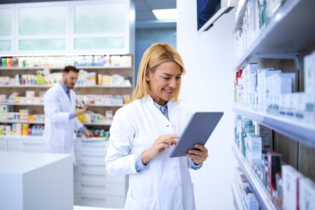 Female pharmacist in white coat checking medicine availability for online orders.
