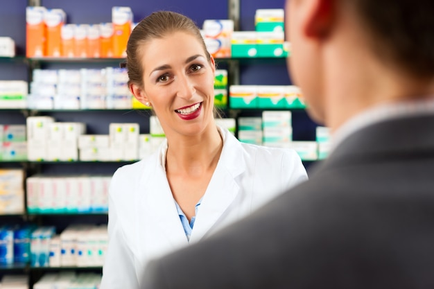 Female pharmacist with client in pharmacy