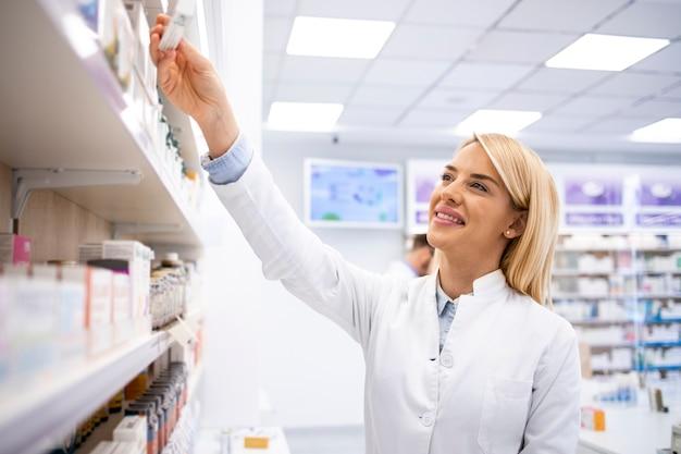 Женский фармацевт, работающий в аптеке, принимая лекарства с полки.