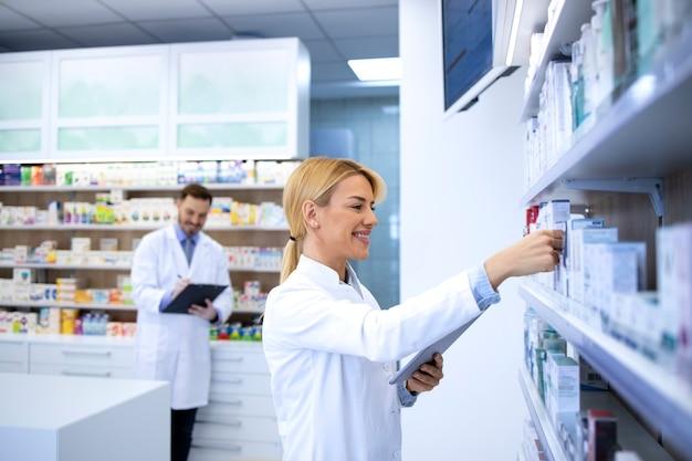 Женщина-фармацевт работает в аптеке и расставляет лекарства на полке.