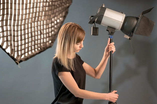 Female photographer adjusting the studio lamp
