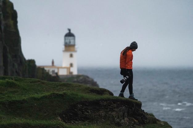 Женщина-фотограф на маяке нейст-пойнт, остров скай, шотландия