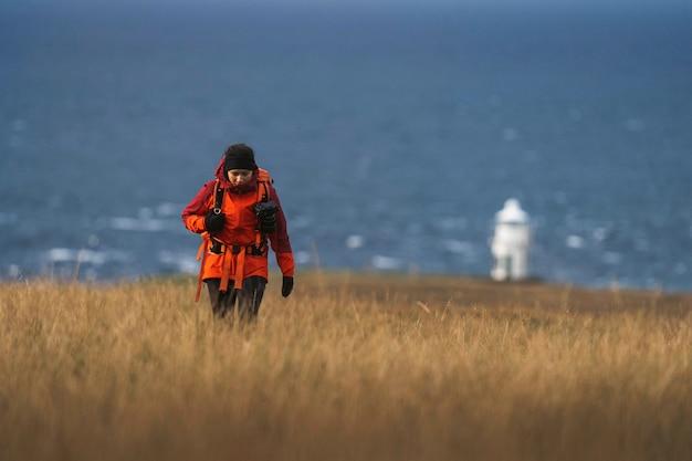 Женщина-фотограф на маяке ватерниш на острове скай, шотландия.