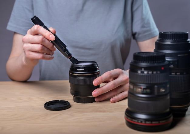 전문 브러시로 카메라 렌즈를 청소하는 여성 사진 작가, 장비, 근접 촬영, 책상에서 먼지 제거에 대한 관심.