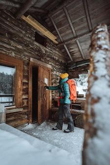 雪に覆われた森の小屋に入る女性写真家