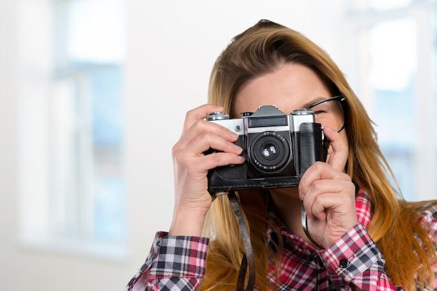Женский фотограф, держащий старинный фотоаппарат