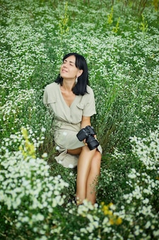 Female photographer holding a camer, sitting outdoors on flower field resting with eyes closed, relaxation, woman hold digital camera in her hands. travel nature photography, space for text, top view.
