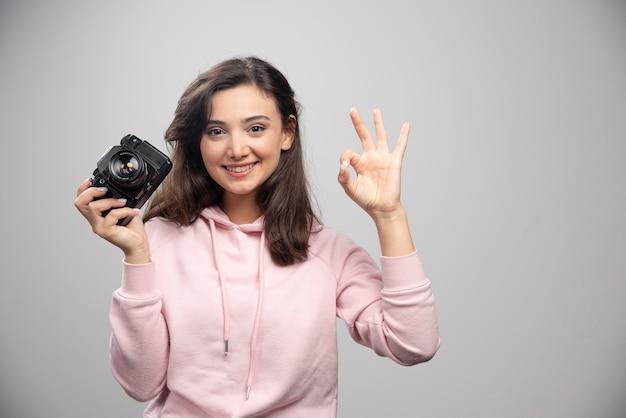 Fotografo femminile che tiene la macchina fotografica e che fa segno giusto.