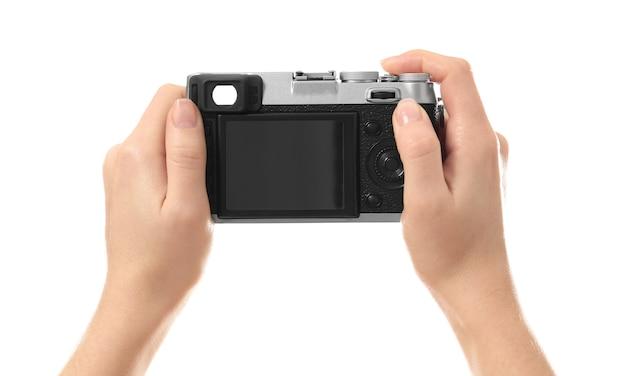 Женский фотограф держит камеру на белом