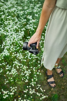Female photographer holding a camera outdoors on flower field landscape, unrecognizable woman hold digital camera in her hands. travel nature photography, space for text.