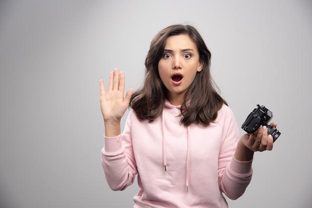 Fotografo femminile che tiene la macchina fotografica con espressione sorpresa.