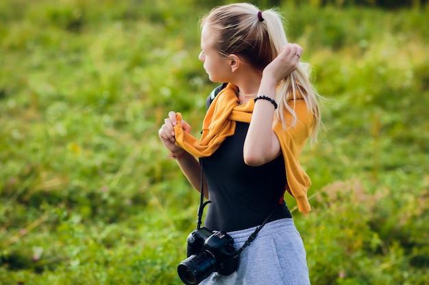 Женский фотограф в поле с фотографированием