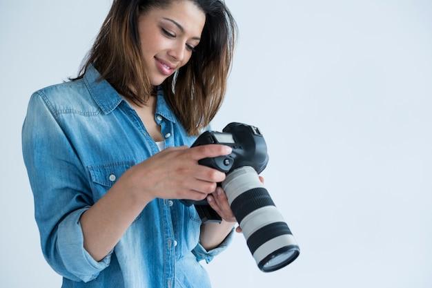그녀의 디지털 카메라에서 캡처 한 사진을 검토하는 여성 사진 작가