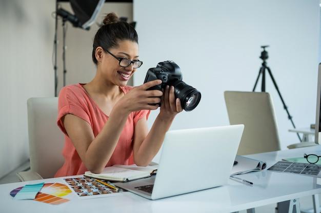 Фотограф женского пола, рассматривающий захваченные фотографии в ее цифровой камере