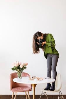 テーブルの上で美容製品を撮影する女性写真家