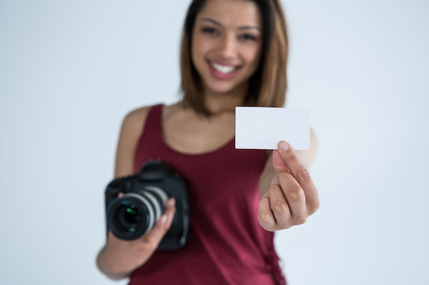 스튜디오에서 방문 카드를 보여주는 여성 사진 작가