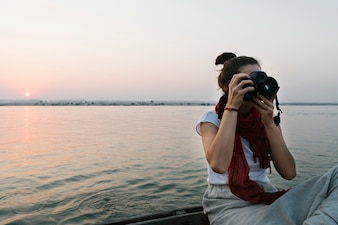 Female photographer sitting on a boat on the River Ganges