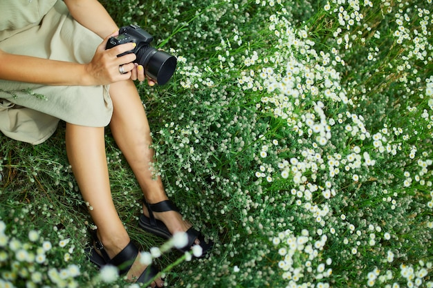 Female photographer sitting outdoors on flower field landscape holding a camera, unrecognizable woman hold digital camera in her hands. travel nature photography, space for text, top view.