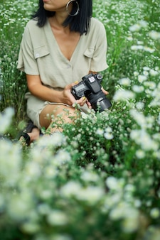Female photographer sitting outdoors on flower field landscape holding a camera, woman hold digital camera in her hands. travel nature photography, space for text, top view.