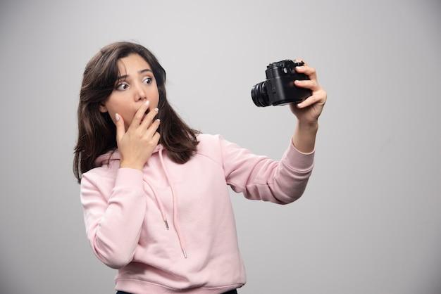 灰色の壁に自分撮りをしている女性写真家。