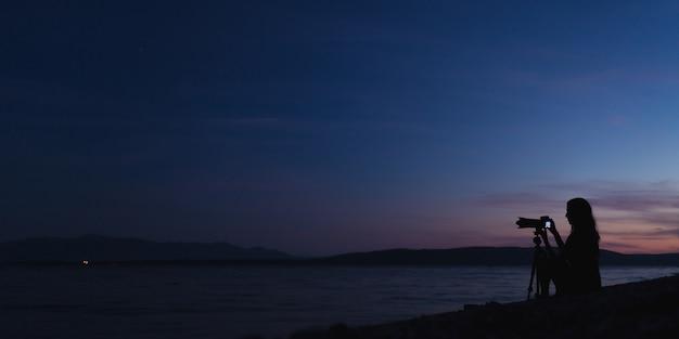夕暮れ時にビーチで写真を撮る女性写真家