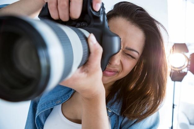 デジタルカメラを持つ女性のカメラマン