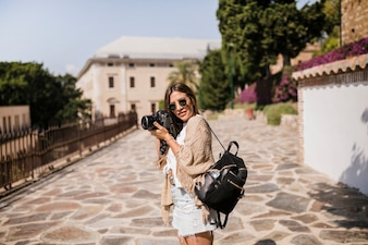 Female photographer with her backpack standing on street