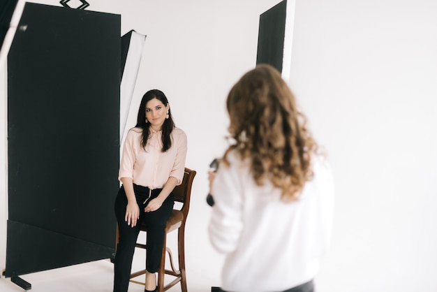 Female photographer with young woman model during shoot