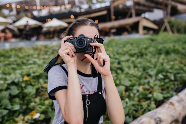 여름 아침에 공원에서 일하는 여성 사진 작가. 도시에서 시간을 보내는 카메라와 백인 여자의 야외 샷.