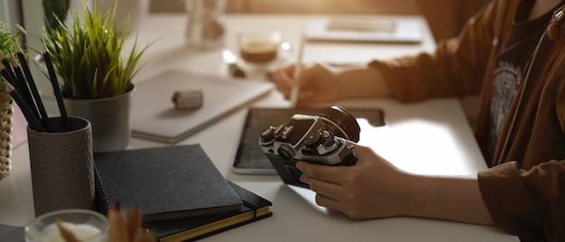 スタイラスペンでタブレットのモックアップに取り組んでいる女性写真家とスタジオの供給とテーブルの上のカメラ