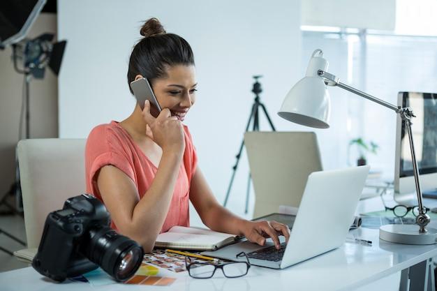 휴대 전화로 얘기하는 동안 노트북을 통해 작업하는 여성 사진 작가