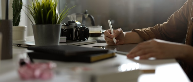 カメラとテーブルの供給のスタジオでテーブルの上のタブレットのモックアップを扱う女性写真家